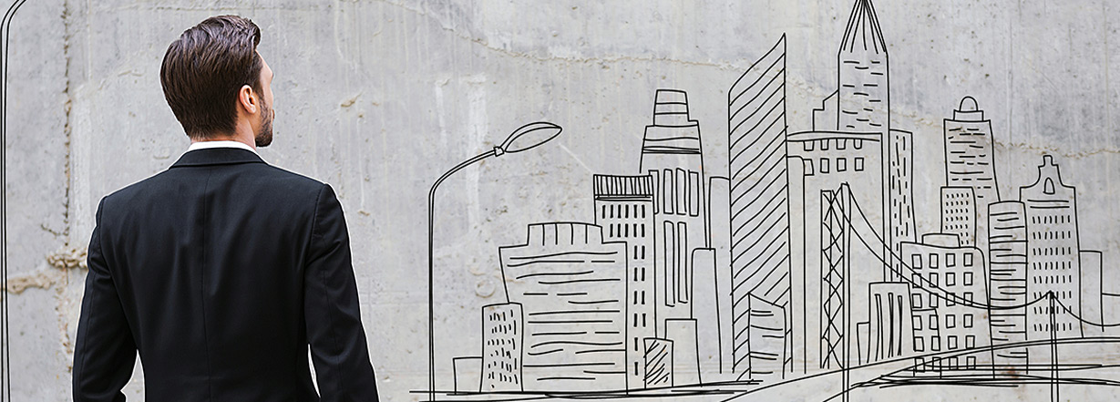 Image of teenager looking at city drawing on wall.