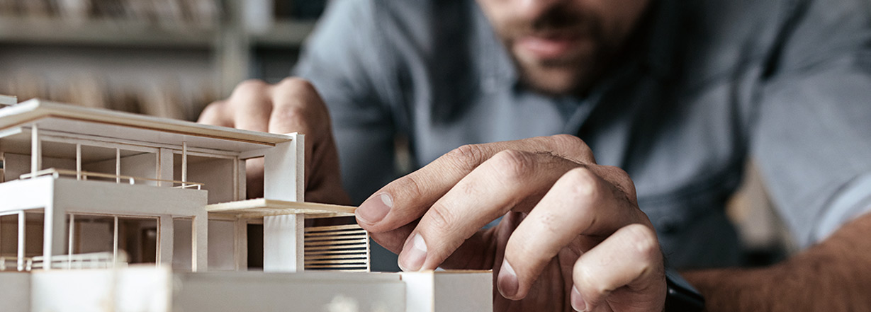 Image of architect working on scale model.